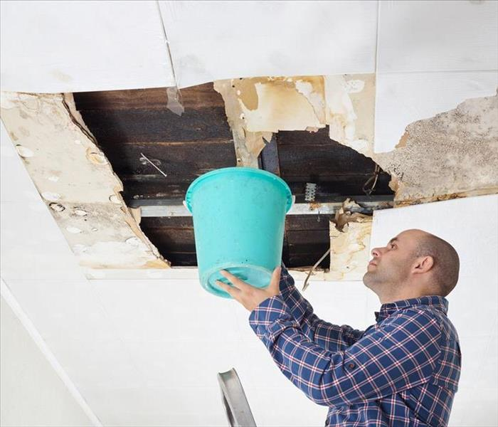 Man holding bucket to catch rain leaking from ceiling