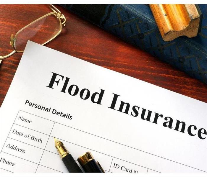 Flood insurance form on a table with two pens on top of the form