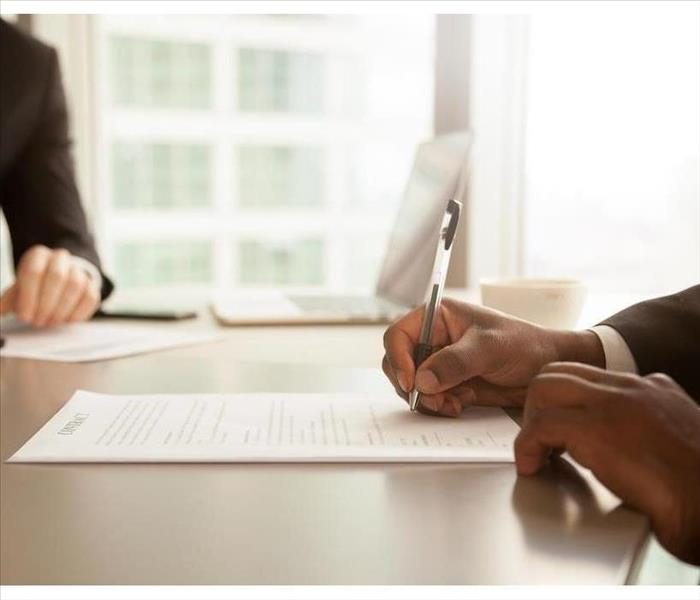 The hands of two people with documents on a desk, one is signing papers.