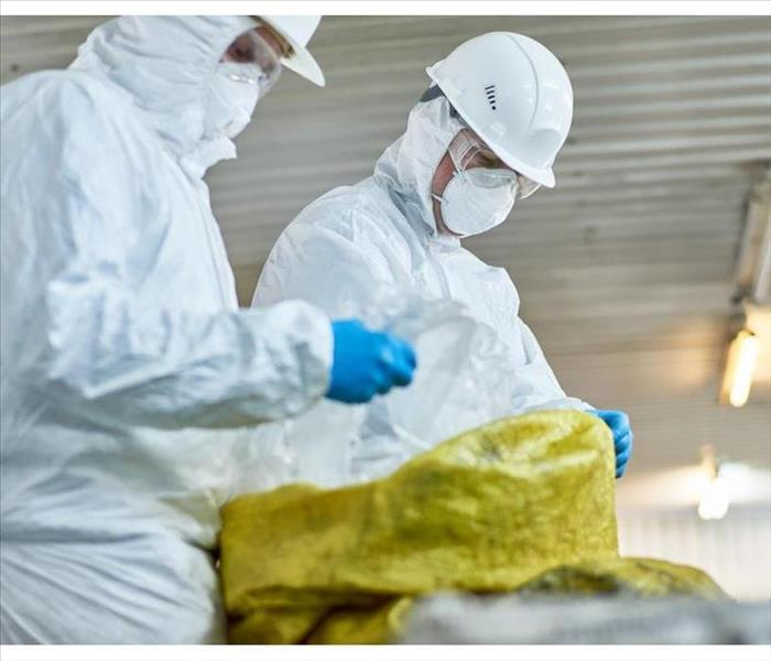 Side view portrait of two workers wearing biohazard suits working at waste processing plant sorting recyclable plastic