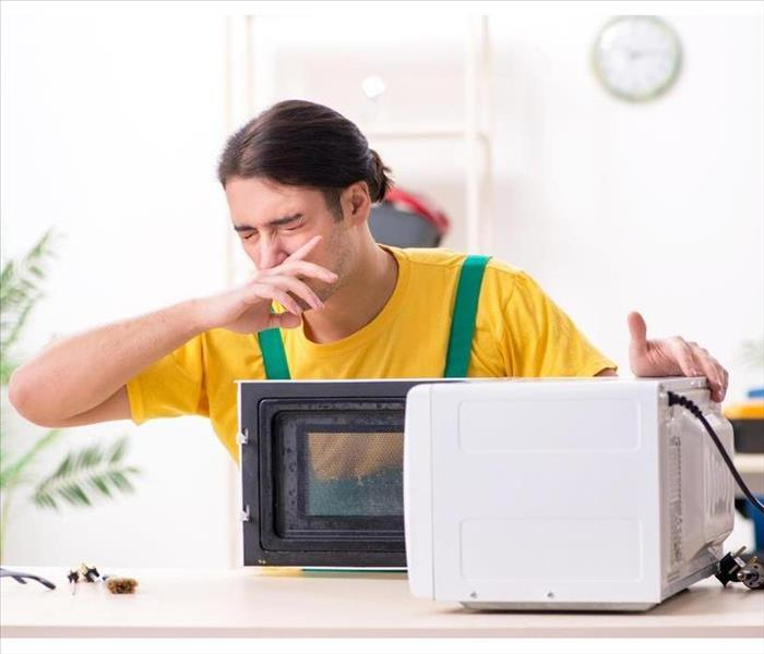 man covering his nose when opening a microwave oven